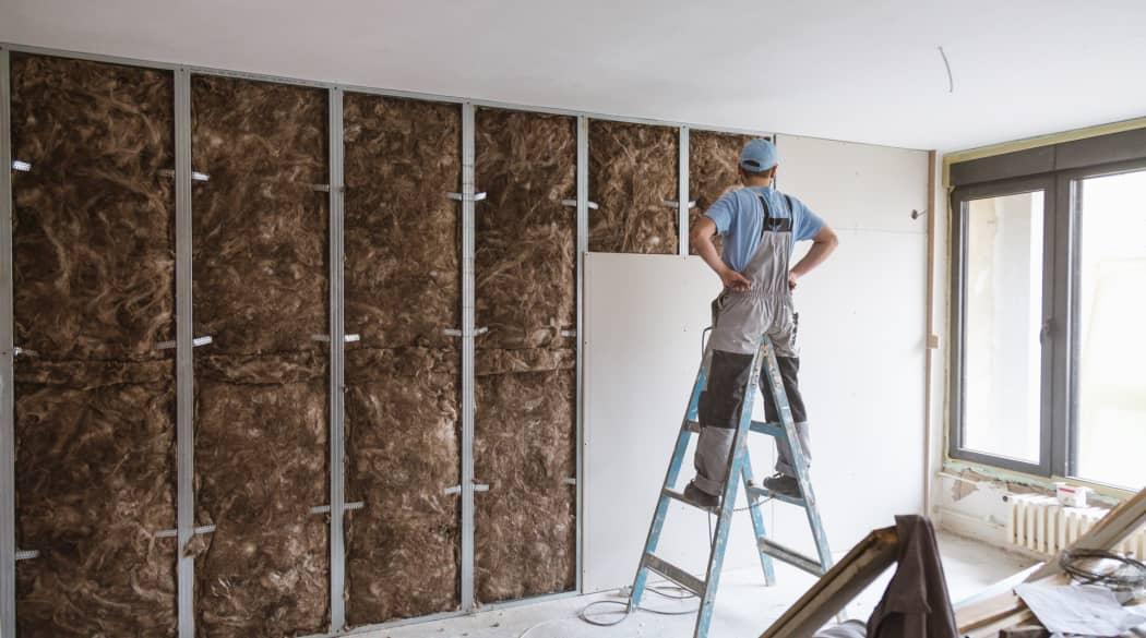 Ein Handwerker steht auf einer Leiter vor einer halbfertigen Trockenbauwand