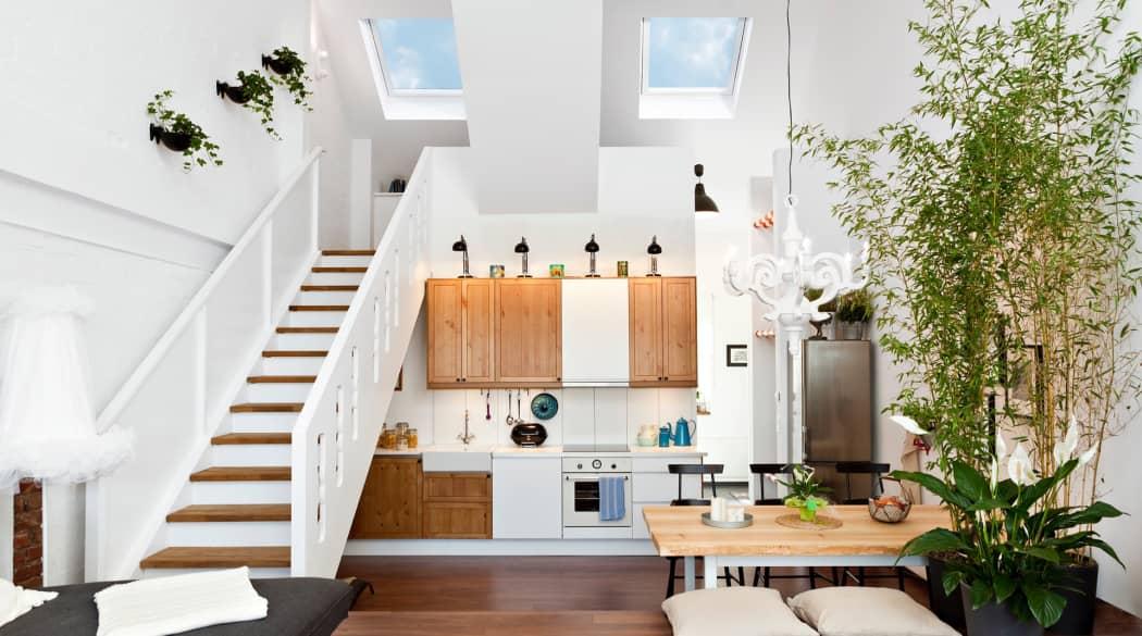 Ein offener Wohnraum mit hellen Wänden und großen Dachfenstern