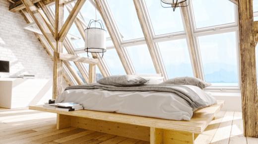 Ein Bett steht auf einem hellen Dachboden vor Dachfenstern
