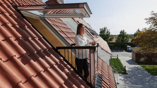 Eine Frau steht auf einem ausklappbaren Balkon