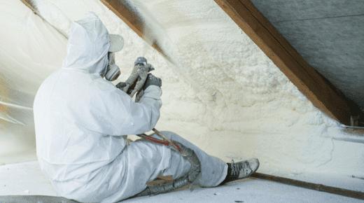Ein Mann im Schutzanzug arbeitet an einer Dachdämmung