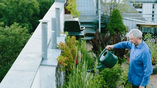 Ein Mann giesst Pflanzen auf der Dachterrasse