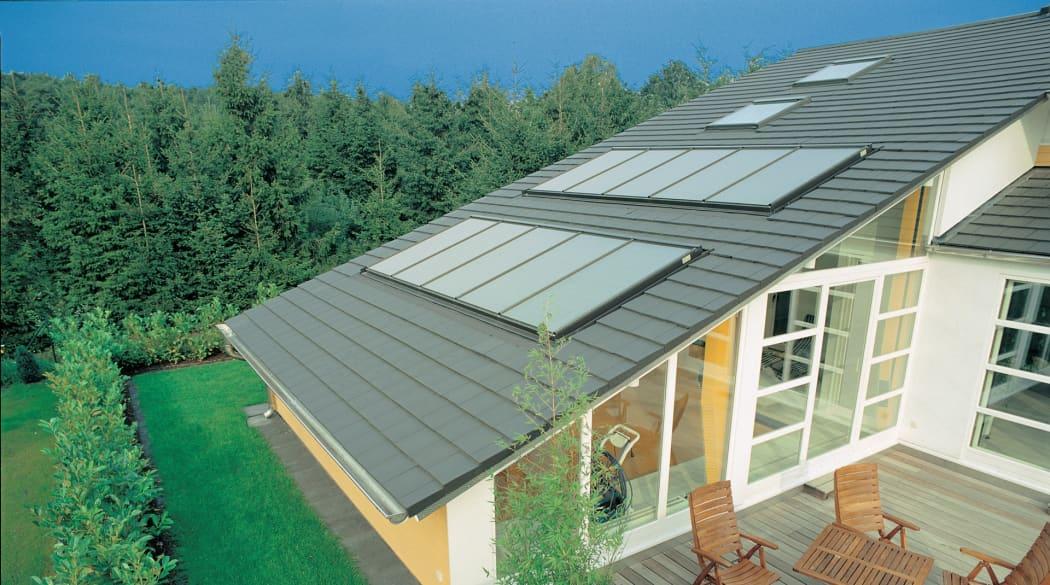 Ein Haus im Grünen mit Solarkollektoren auf dem Dach