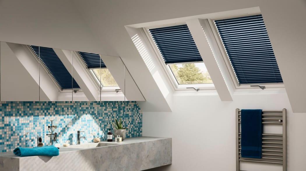 Weisses Badezimmer unterm Dach mit blauen Dachfensterjalousie