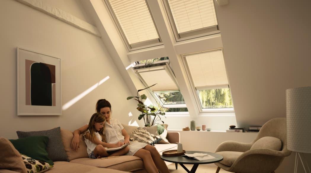 Mutter und Kind auf der Couch im Dachgeschoss lesen ein Buch(A)