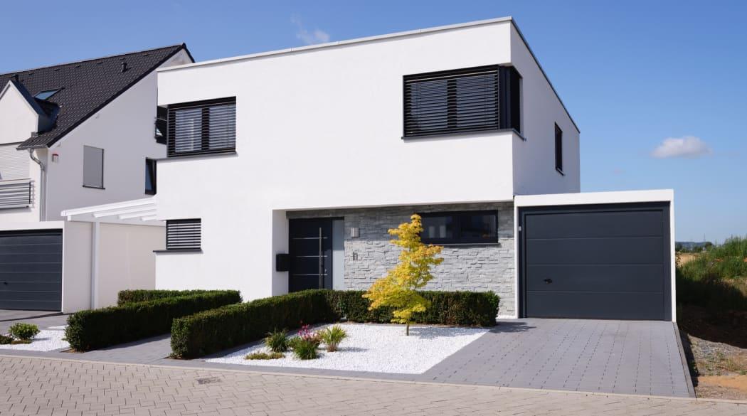 Ein weisses Eigentumshaus mit Flachdach