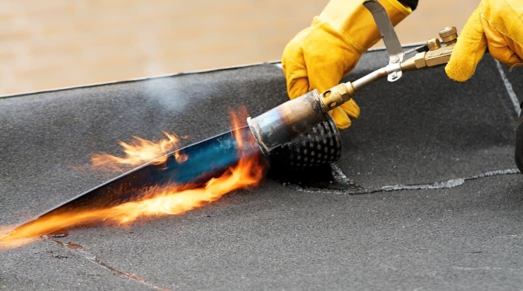 Bitumenbahnen werden mit einer Flamme erhitzt