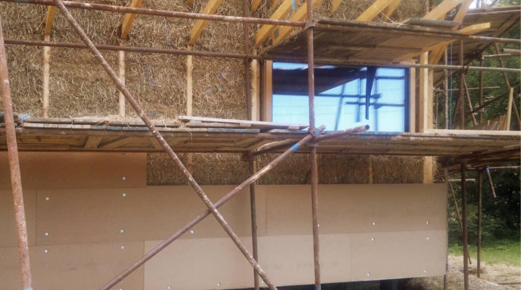 Dämmung eines Passivhauses: Strohballen werden eingestapelt