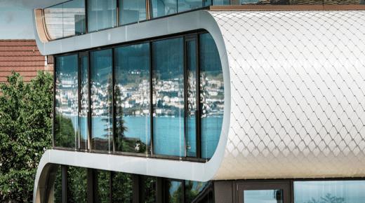 Das Flexhouse von der Seite gesehen: in der Glasfassade spiegelt sich die Landschaft