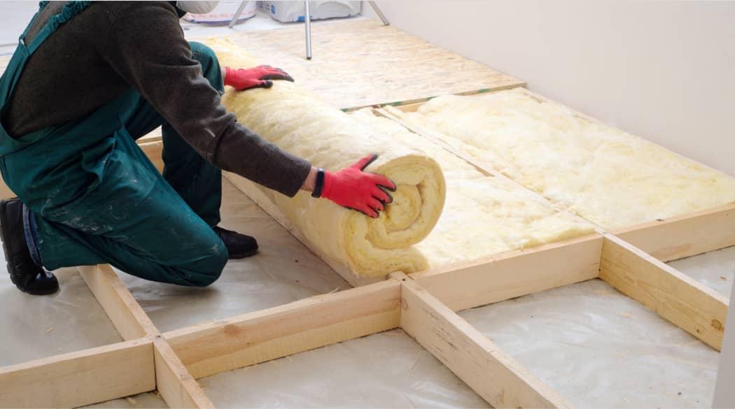 Ein Handwerker mit roten Handschuhen rollt eine Wärmedämmung auf einem Dachboden aus