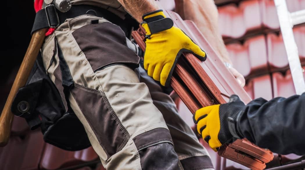 Dachdecker suchen und finden: zwei Dachdecker auf dem Dach mit gelben Handschuhen reichen sich einen Dachziegel