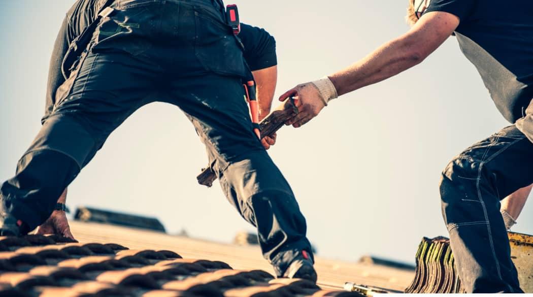 Dachdecker suchen und finden: Zwei Dachdecker arbeiten auf dem Dach