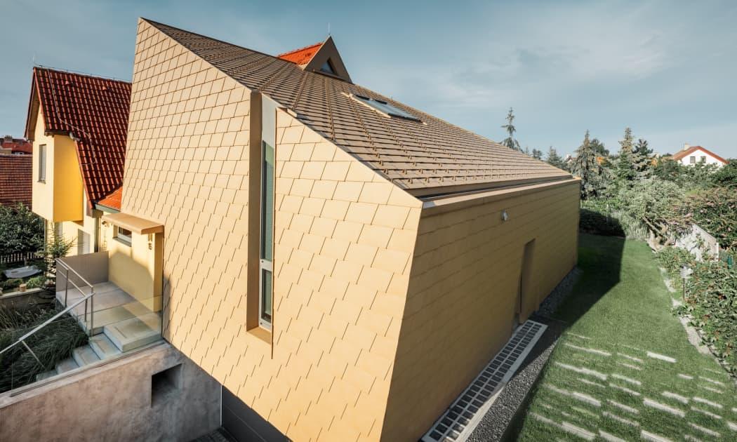 Ein Einfamilienhaus in Prag, gedeckt mit gelben Dach- und Wandschindeln aus Aluminium