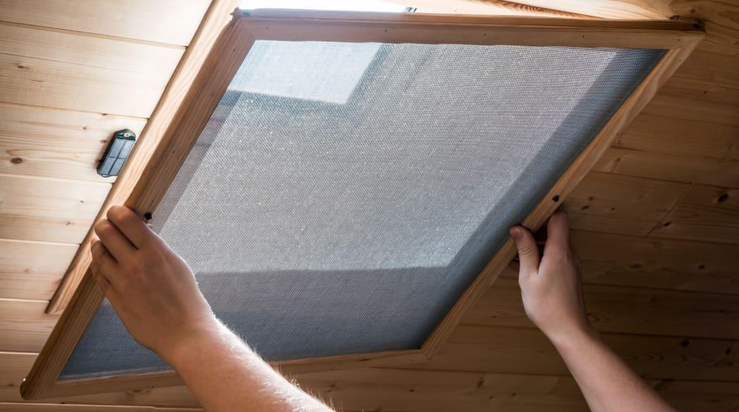 Eine Frau setzt ein Fliegengitter von innen auf ein Dachfenster