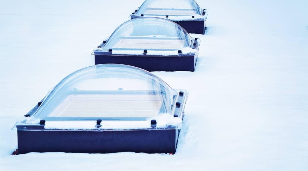 Drei Lichtkuppeln von außen gesehen auf einem schneebedeckten Flachdach