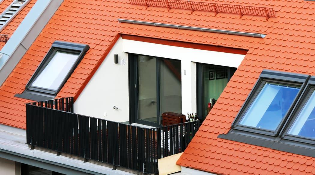 Dachloggia: ein Dach mit roten Ziegeln und Dachloggia in der Mitte, daneben Dachfenster