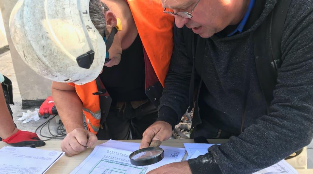 Dachausbau mit Innenausbau: Handwerker beugen sich über einen Bauplan