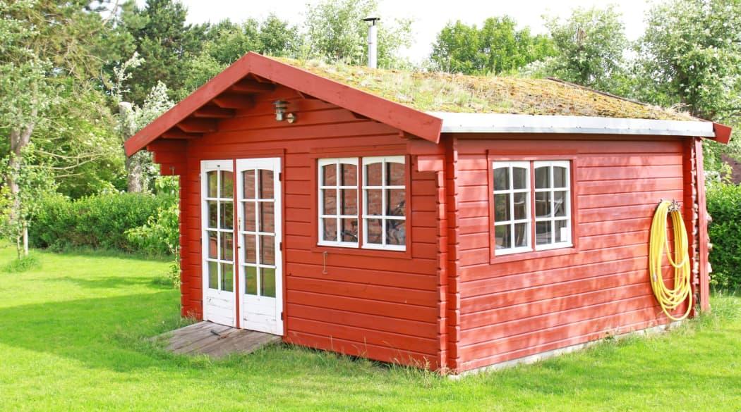 Rotes Gartenhaus mit Gründach