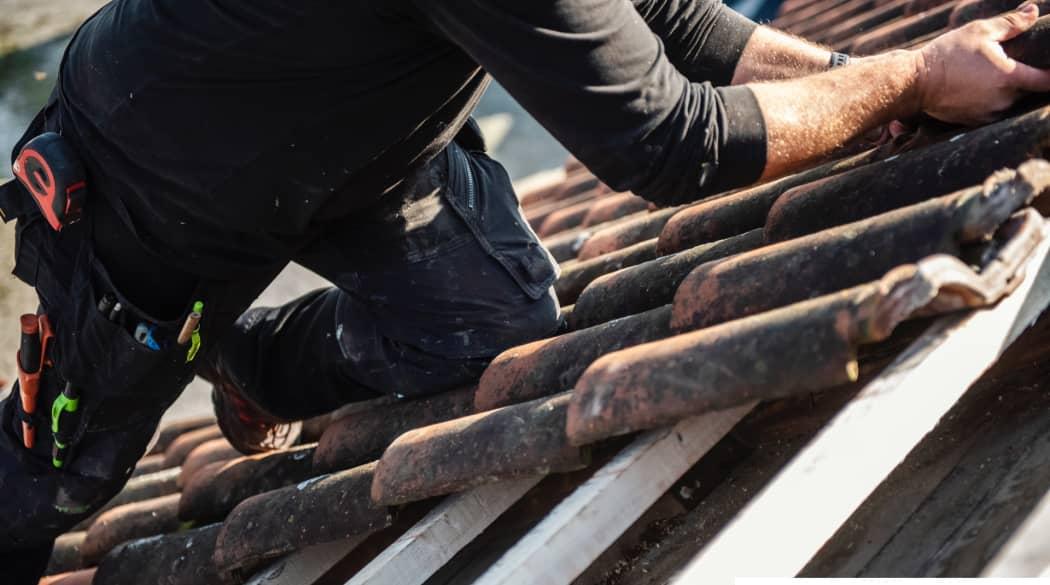 Kosten einer Dachsanierung: ein Dachdecker hantiert mit rot-schwarzen Ziegeln auf dem Dach