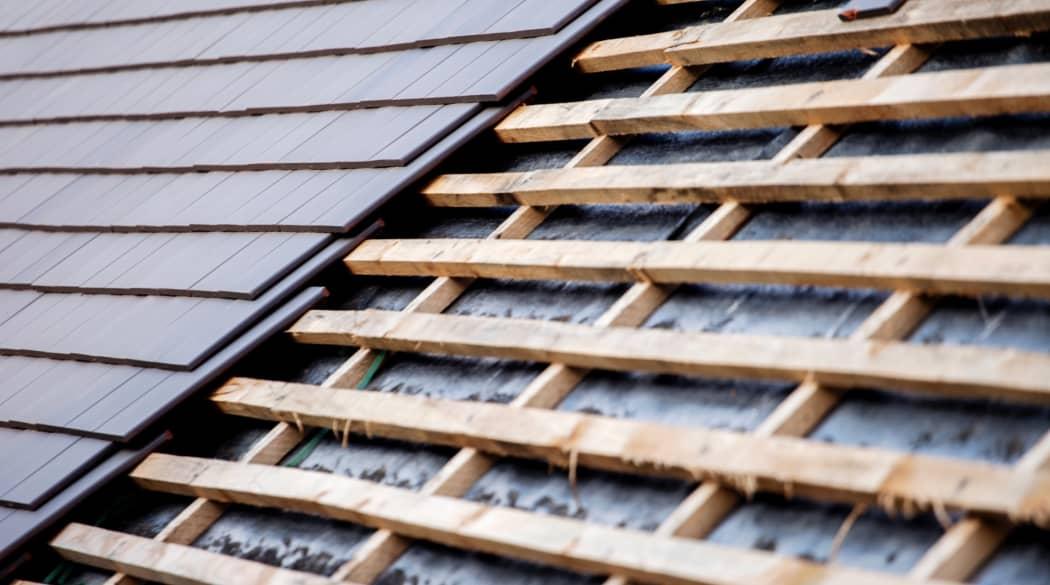 Kosten einer Dachsanierung: ein halb gedecktes Dach mit dunkelgrauer Bedeckung