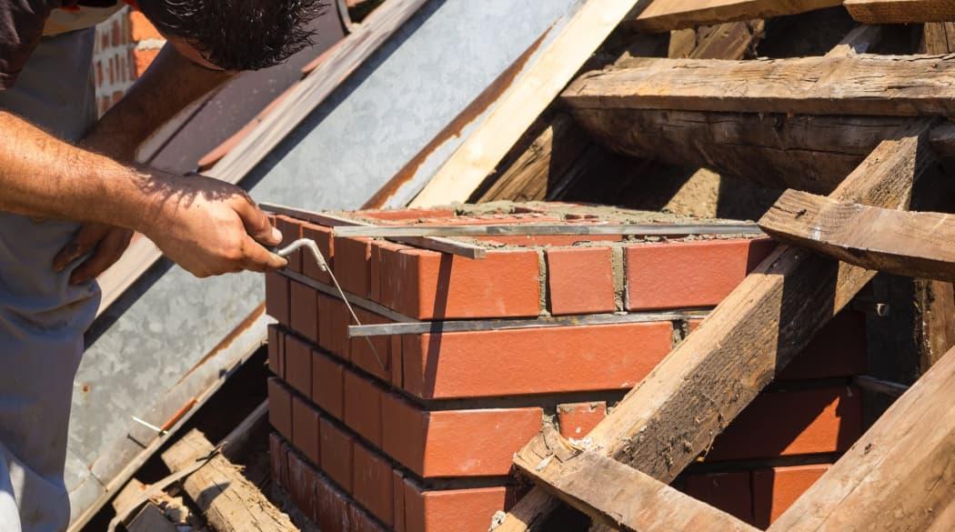 Kosten einer Dachsanierung: ein Handwerker arbeitet an einem Schornstein aus roten Backsteinen