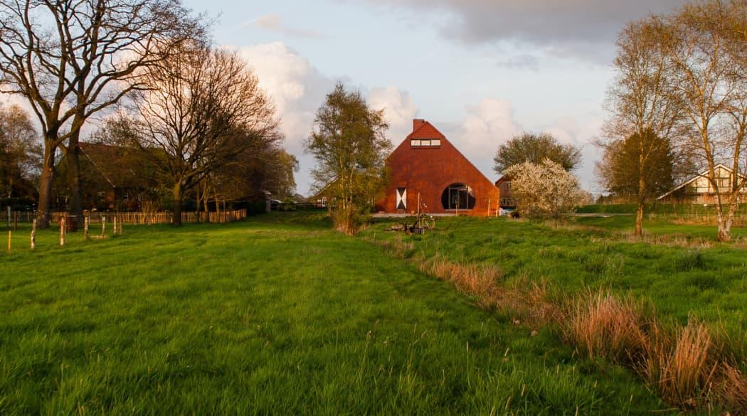 Thomas Kröger Architekt: das Haus am Deich aus der Ferne gesehen - ein roter Farbtupfer in grüner Landschaft
