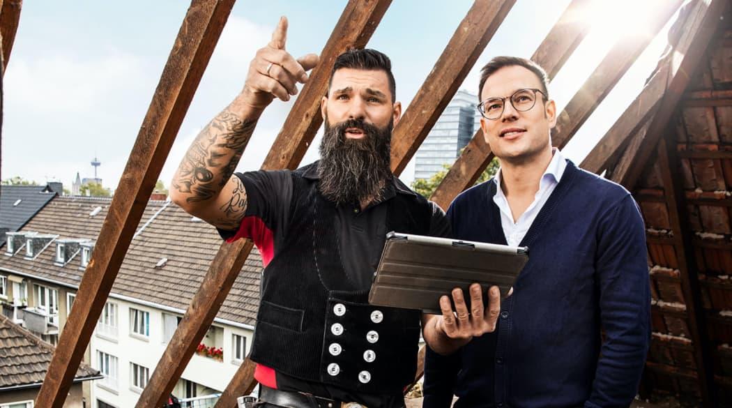 Experten für das Dach: ein Dachdecker und der Bauherr stehen auf dem Dachboden eines bereits abgedeckten alten Daches
