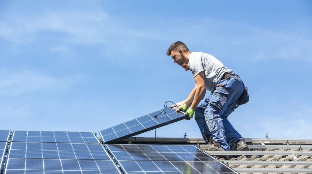 Experten für das Dach: ein Dachdecker verlegt auf einem Dach Solarpanele