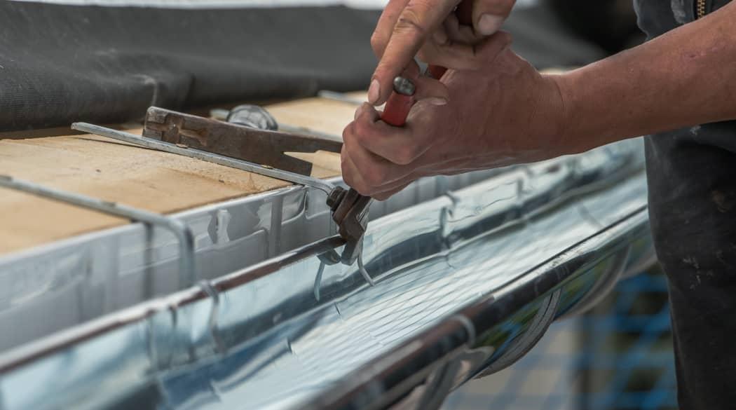 Experten für das Dach: ein Spengler bearbeitet eine Dachrinne aus Metall