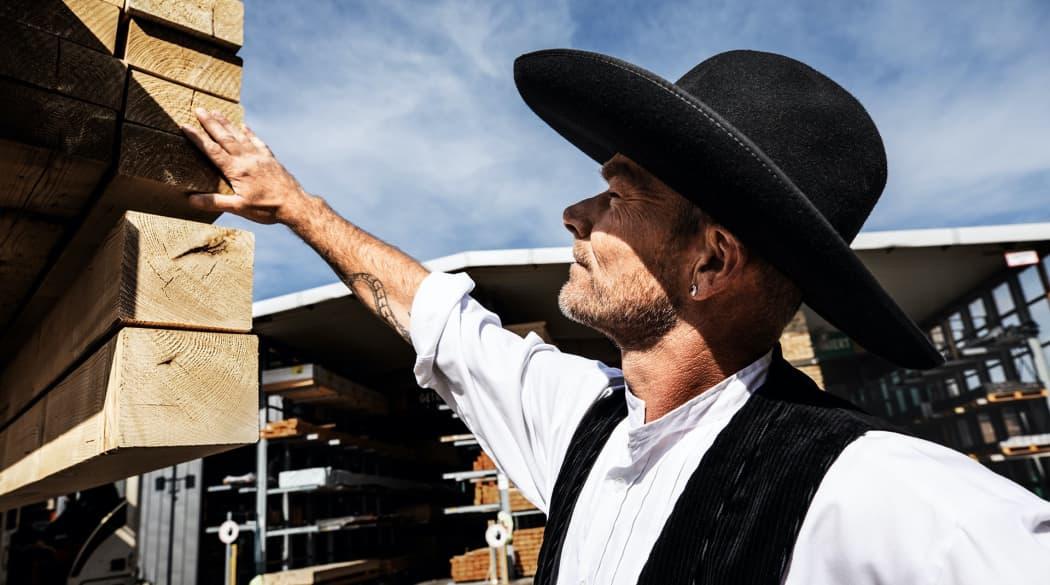 Experten für das Dach: ein Zimmermann in traditioneller Tracht betrachtet einen Stapel von Holzlatten
