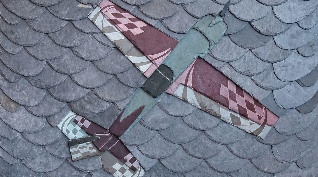 Schieferdeckung: ein Schieferornament in Form eines kleinen Flugzeugs