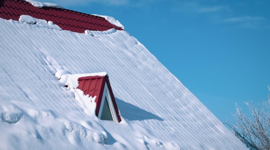 Ihr Dach im Winter: ein Steildach mit roten Ziegeln und halb bedeckt von Schnee