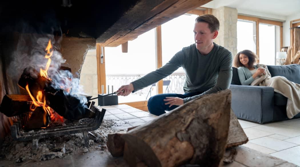 Ihr Dach im Winter: ein junger Mann kniend vor einem Kaminfeuer