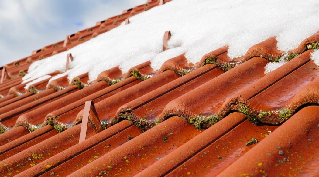 Ihr Dach im Winter: Ein Steildach mit roten Ziegeln und Schneefanghaken leicht mit Schnee bedeckt