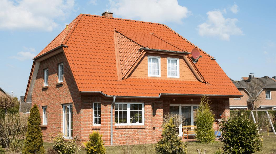Dachziegelfarbe: ein Haus mit hellroter Backsteinfassade und orangenem Dach