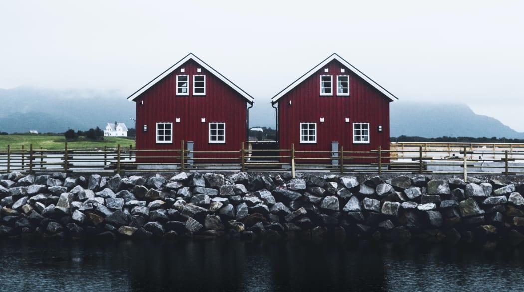 Satteldach: zwei dunkelrote Holzhäuser mit Steildach