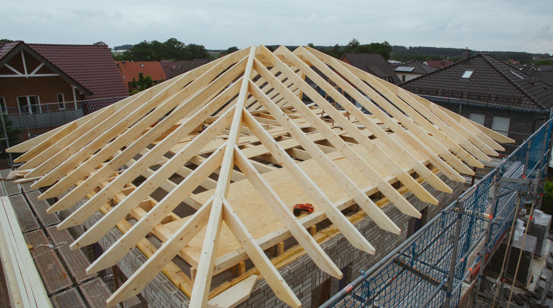 Holz für den Dachstuhl: Ein Haus mit noch uneingedecktem hölzernen Dachstuhl