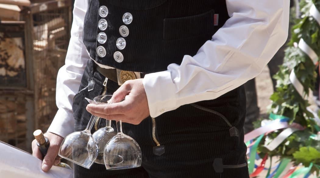 Dachdecker mit drei Weingläsern in der Hand