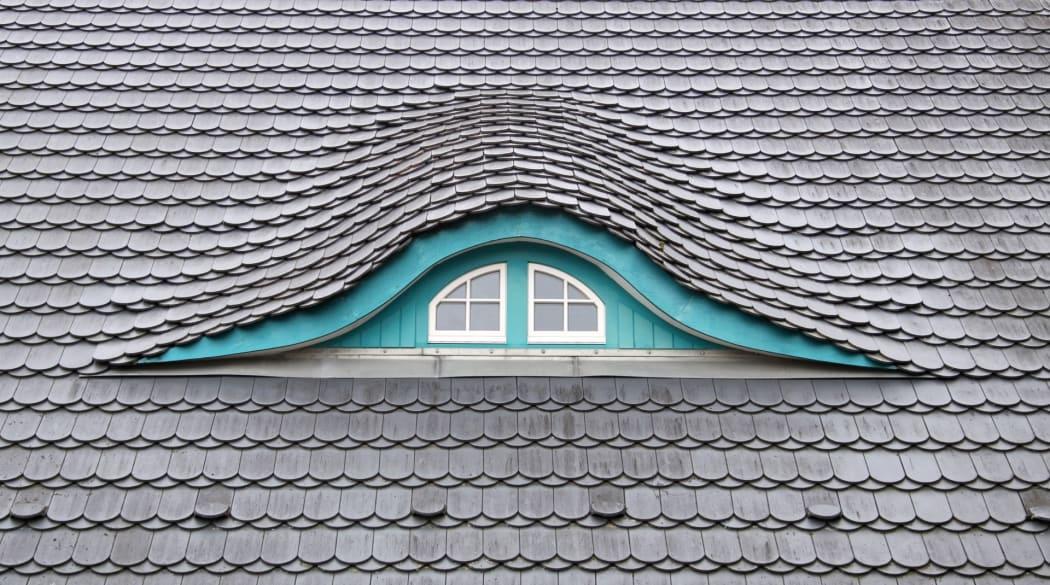 Ein Dach mit Biberschwanzziegeln und einer Fledermausgaube