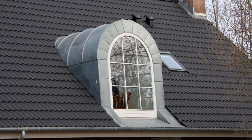 Ein Dach mit einer graumetallischen Tonnengaube