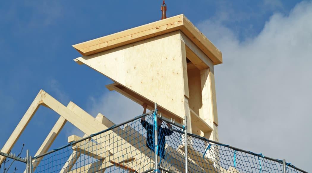 Dachgauben: eine hölzerne Flachdachgaube wird hängend an einem Kran auf den Dachstuhl gesetzt