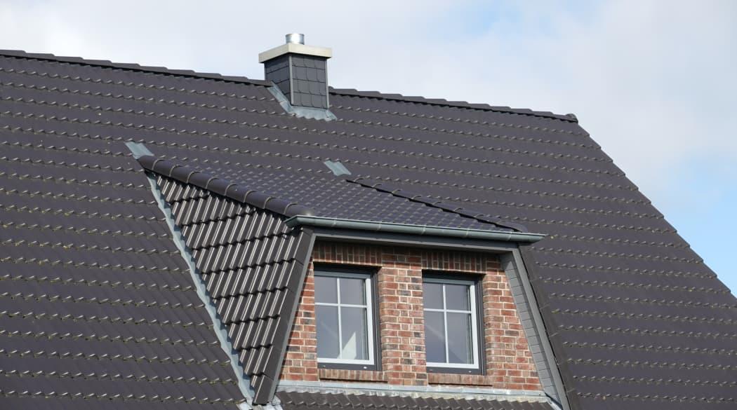 Dachgauben: eine Trapezgaube auf einem dunklen Hausdach