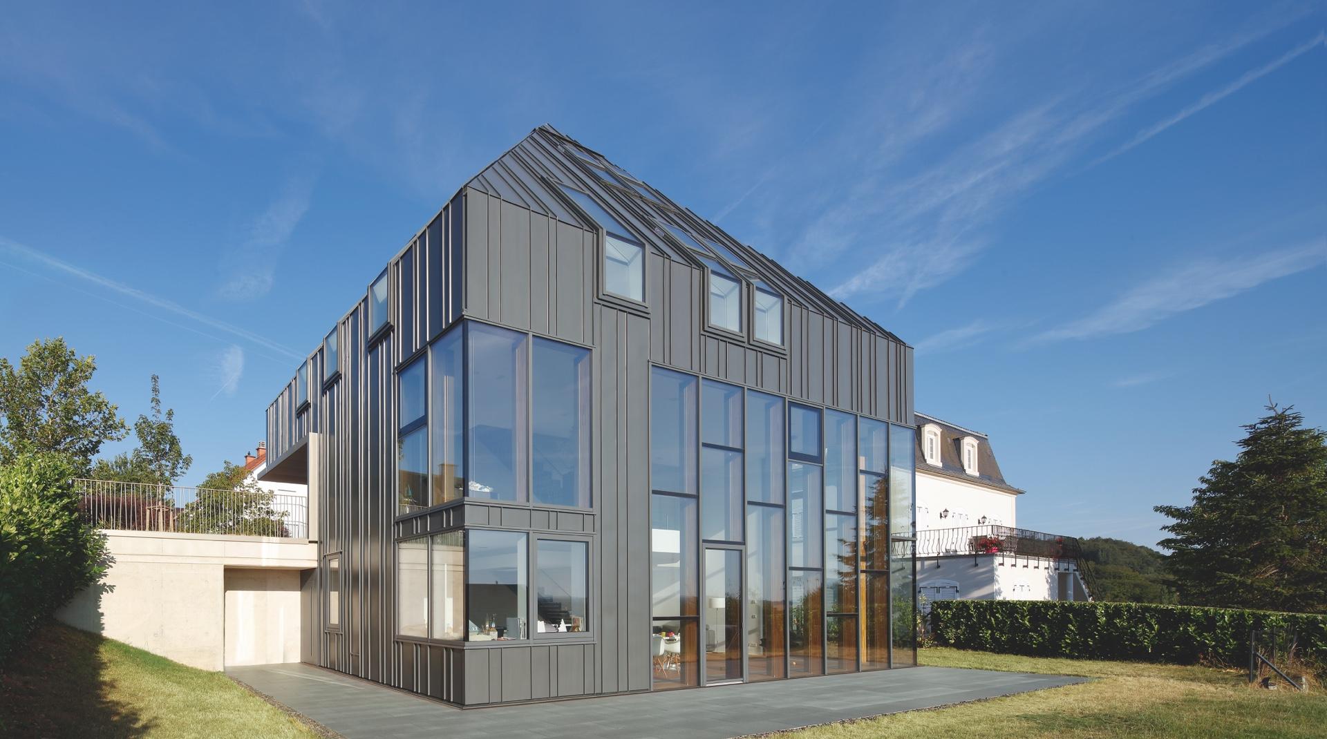 Titanzink-Haus in Gonderange: die Ansicht von der Hinterseite, eine Fassade aus Glas und dunklem Metall