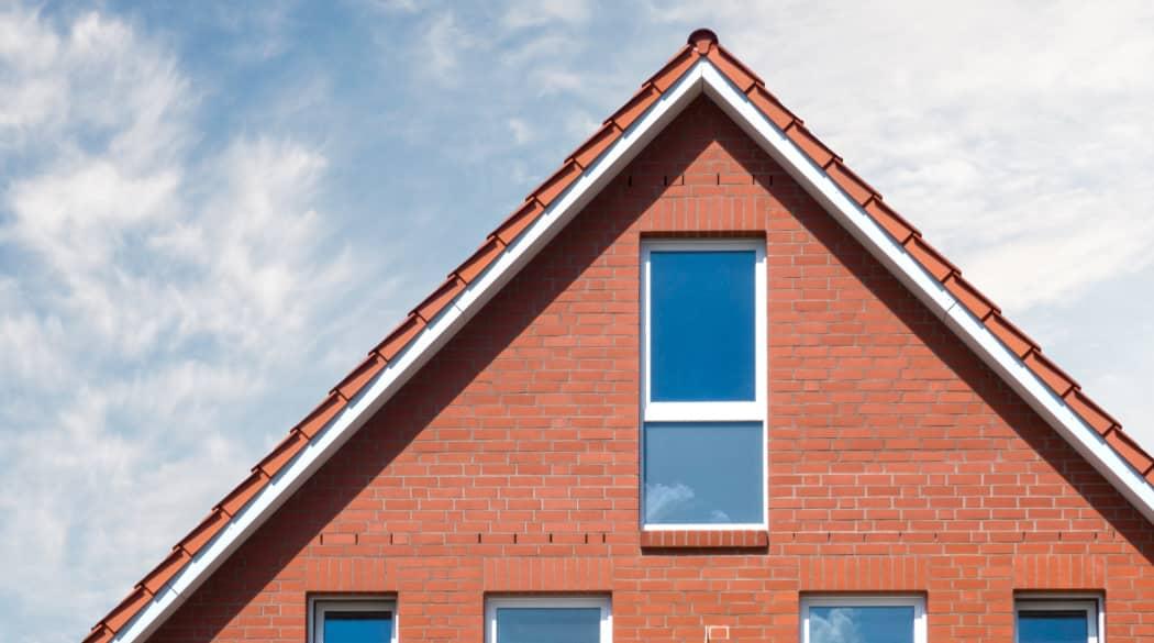 Traditionelle Dächer: ein Haus mit roten Backsteinen und rotem Satteldach