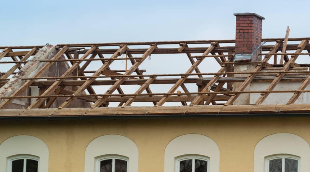 Das Dach sanieren: ein alter, abgedeckter Dachstuhl