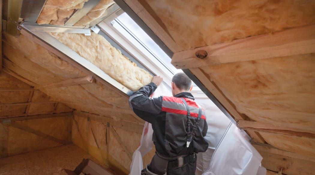 Das Dach sanieren: Ein Mann dämmt ein Dachfenster