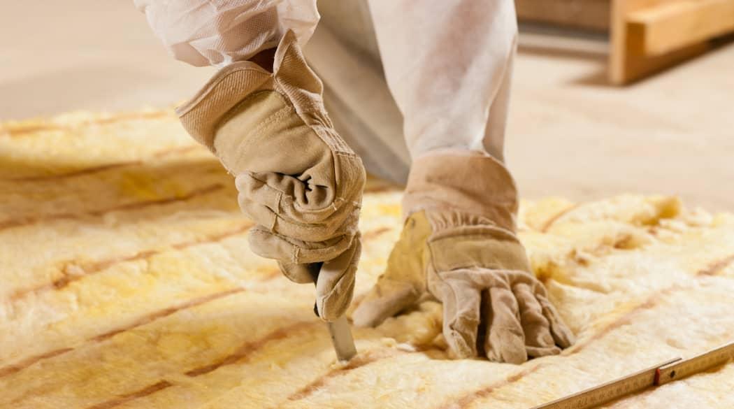 Handwerker schneidet Glaswolle
