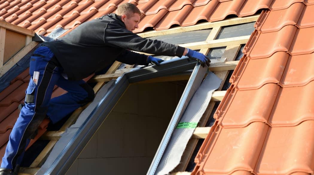Dachfenster austauschen: ein Mann baut ein Dachfenster ein