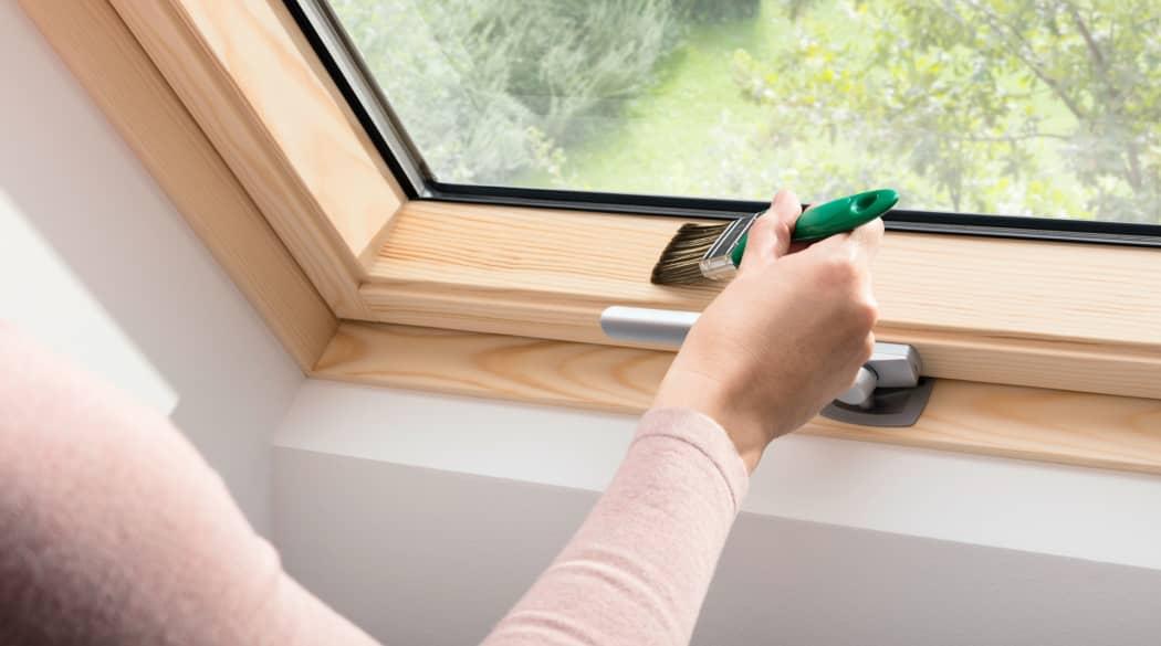 Dachfenster austauschen: eine Frau streicht den Holzrahmen eines Dachfensters mit Pflegeöl ein