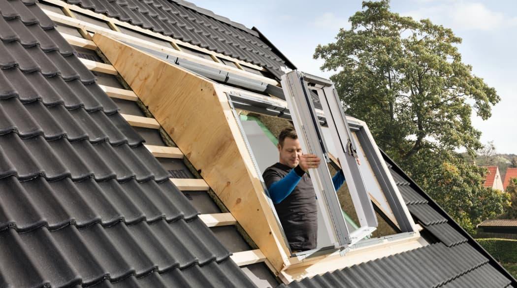 Dachfenster austauschen: ein Handwerker baut ein Dachfenster in den Rahmen ein